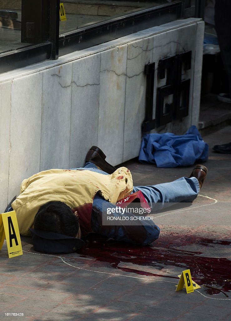 A body lies in a street at the 'Zona Rosa', a commercial and tourist area of Mexico City, on February 15, 2013. The man was killed by an unidentified gunman. AFP PHOTO/Ronaldo Schemidt