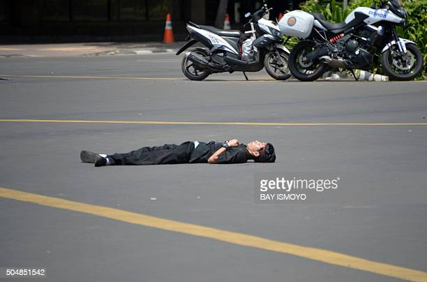 A body lies in the street after after a series of blasts hit the Indonesia capital Jakarta on January 14 2016 A series of bombs killed at least three...