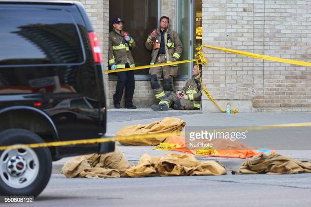 A body lies on the pavement covered in an orange tarp after 10 people were killed and 15 people injured in a deadly van attack in Toronto Ontario...