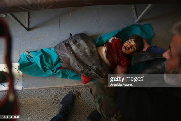 Body of a child is seen as a man strokes his head after Assad Regime warplanes carried out aerial attacks on residential areas in Kafr Batna district...