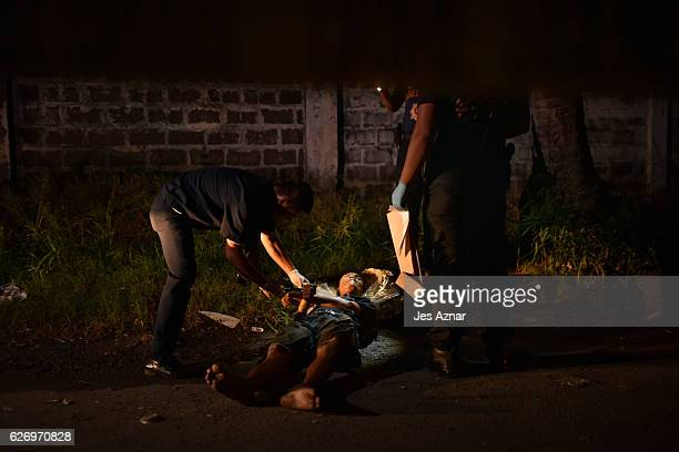 Body of a still unidentified man wrapped in tape is inspected by crime scene investigators on November 17, 2016 in Paranaque city, Philippines. Metro...