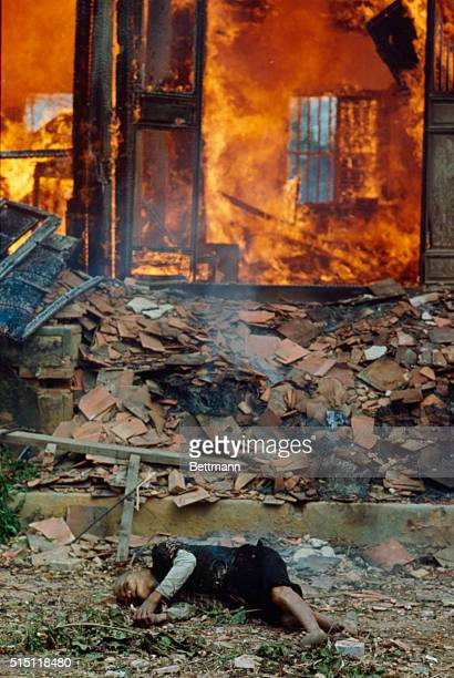 Body of a victim lies in front of a burning house following US air and artillery attacks on a village about 8 km south of Quang Tri where US 1st Cav...