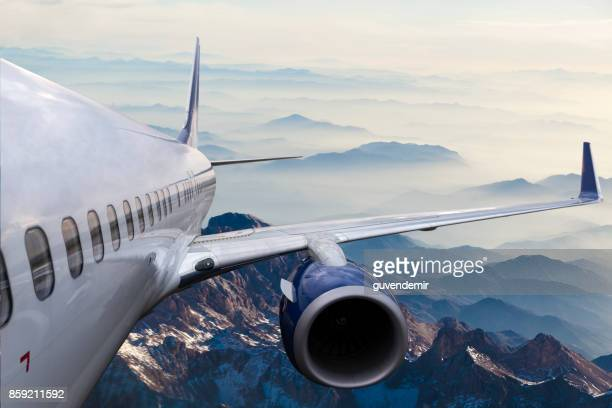 body of an airplane flying above cloud at dusk - flying stock photos and pictures