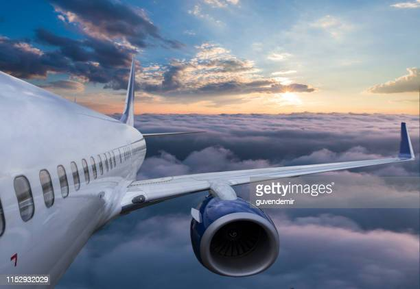body of an airplane flying through clouds at sunset - aircraft wing stock pictures, royalty-free photos & images