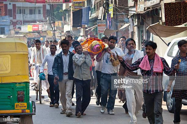 Body of dead Hindu woman carried in procession in street for funeral pyre cremation by the Ganges Varanasi Benares Northern India