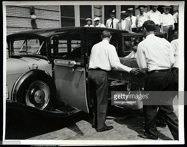 Body of John Dillinger slain outlaw being removed from the mortuary at 4506 Sheraton Road and placed in a shabby home town hearse for his last ride...