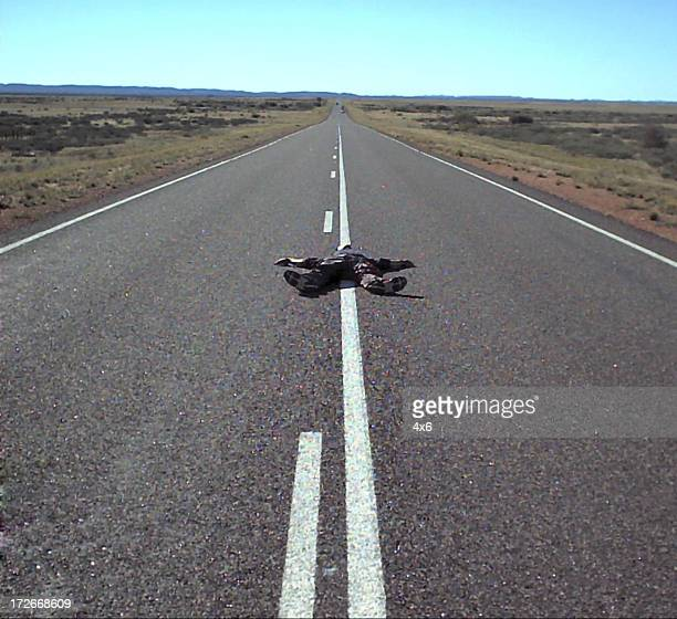 body on long stretch of road
