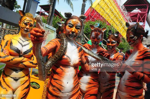 Body painted women pose with a snake during a running activity on Women's Day at Sanya Color Zoo on March 8 2017 in Sanya Hainan Province of China...