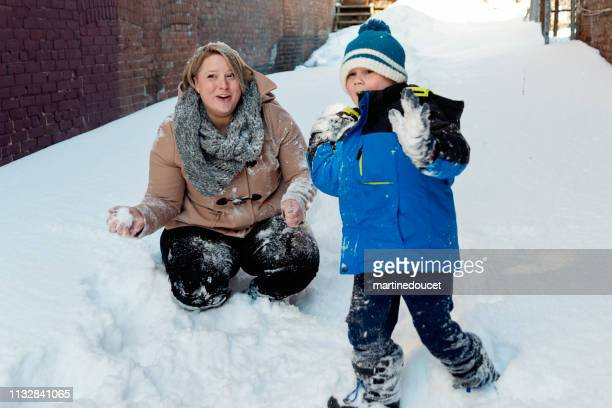 Body positive mother playing with her son outdoors in snow.