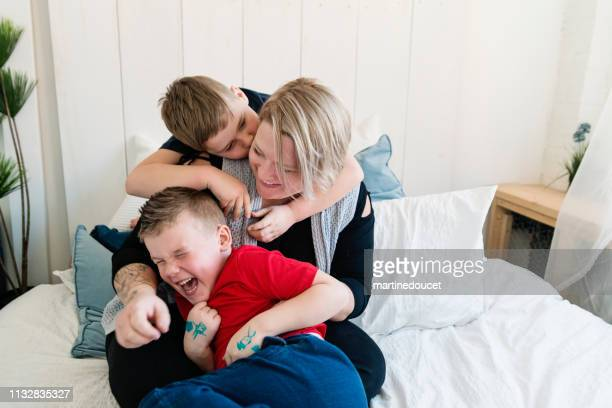 "body positive mother playing with her two sons on a bed. - ""martine doucet"" or martinedoucet stock pictures, royalty-free photos & images"