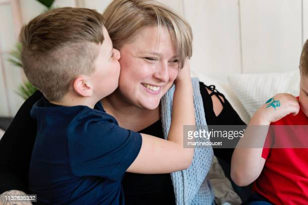 Body positive mother playing with her two sons on a bed.