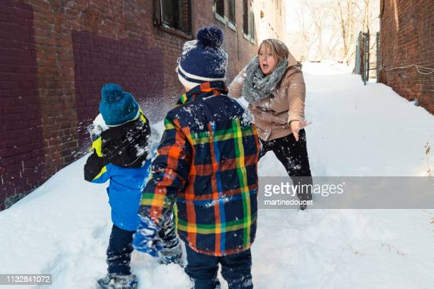 Body positive mother playing with her two sons outdoors in snow.