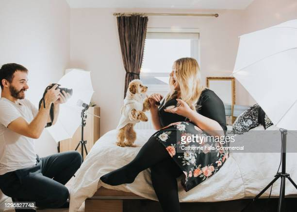 body positive social media icon and her dog perform in a small bedroom with her boyfriend as the camera operator - like button stock pictures, royalty-free photos & images