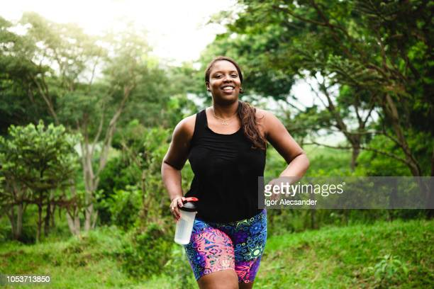 body positive woman exercising in nature - heavy stock pictures, royalty-free photos & images