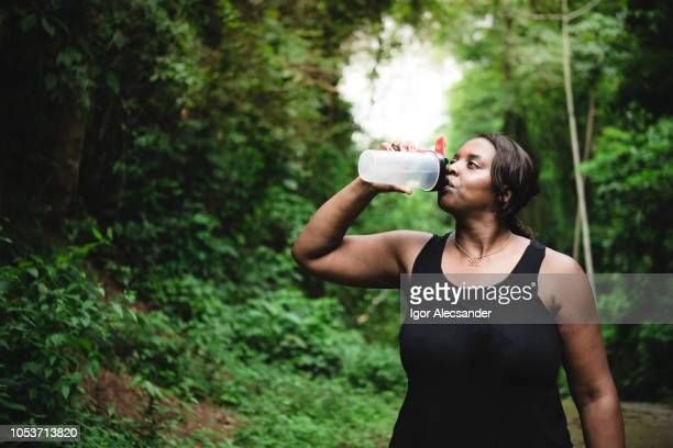 body positive woman hydrating during the cooper - drinking water stock pictures, royalty-free photos & images