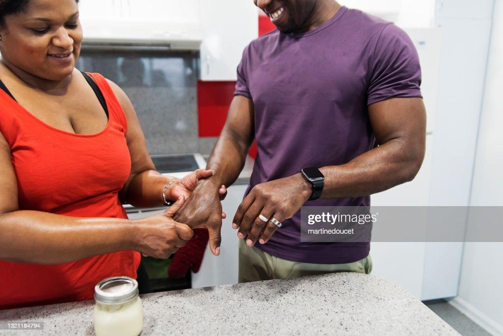 Body positive woman rubbing on homemade hand cream on husband hands. : Stock Photo