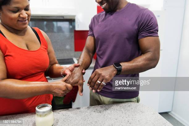 """body positive woman rubbing on homemade hand cream on husband hands. - """"martine doucet"""" or martinedoucet stock pictures, royalty-free photos & images"""