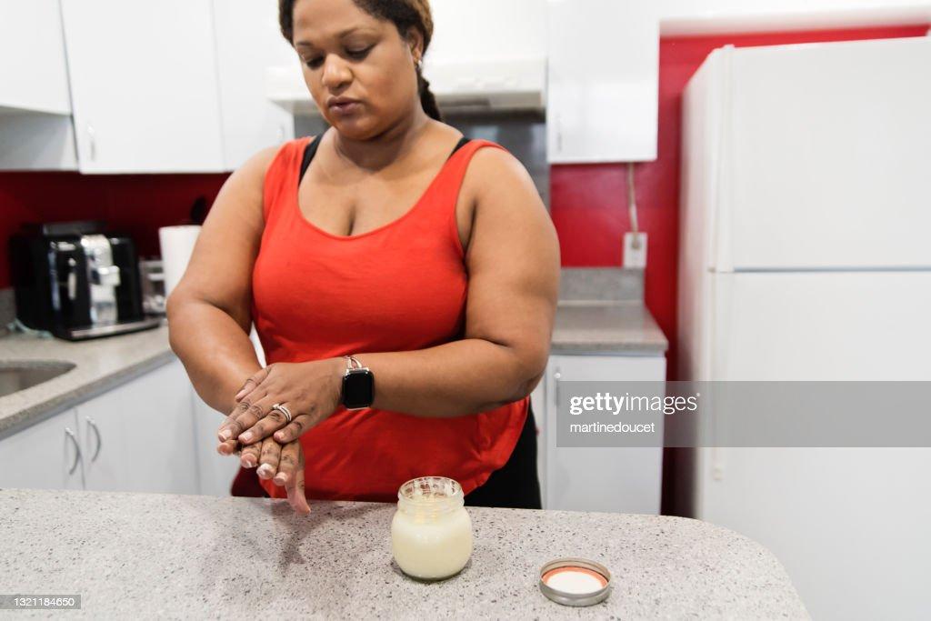 Body positive woman rubbing on homemade hand cream. : Stock Photo