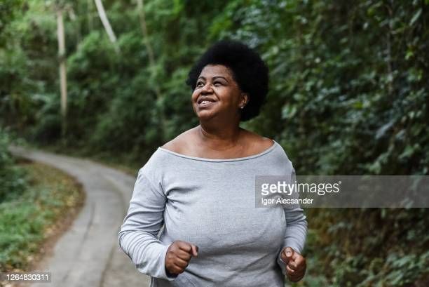 corpo positivo mulher correndo no parque natural - gordo - fotografias e filmes do acervo