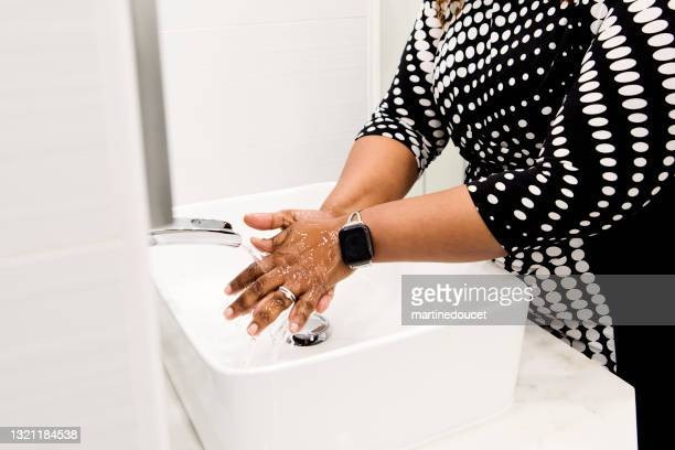 """body positive woman washing hands in bathroom sink. - """"martine doucet"""" or martinedoucet stock pictures, royalty-free photos & images"""