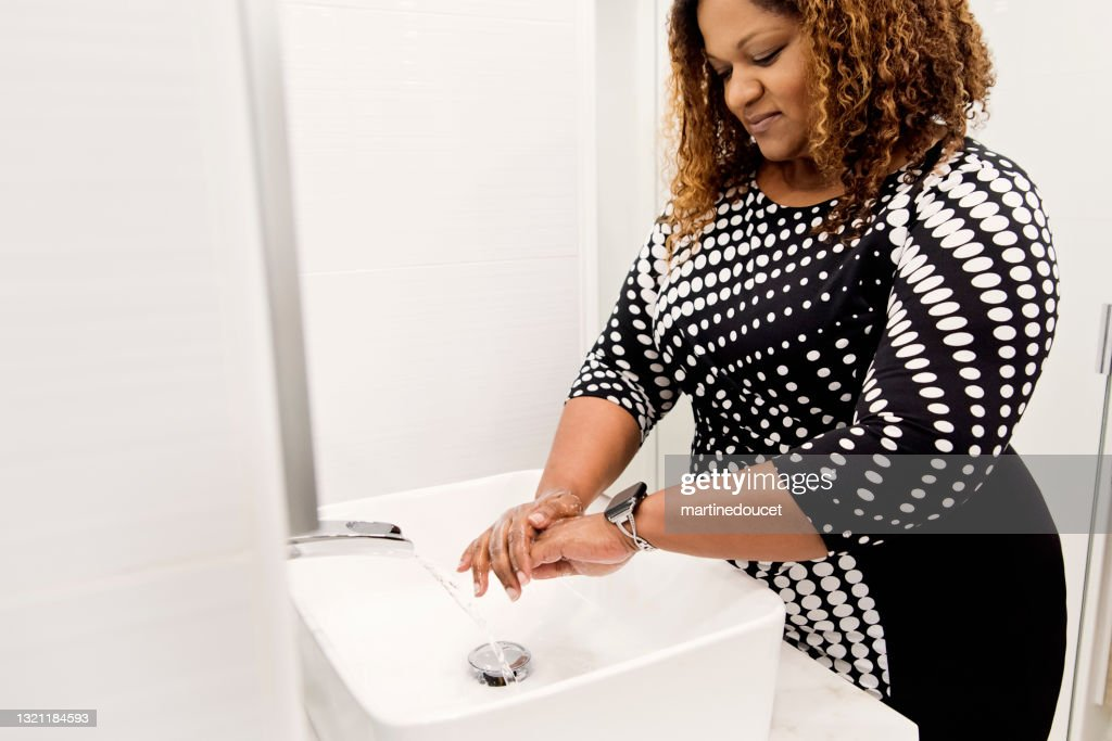 Body positive woman washing hands in bathroom sink. : Stock Photo