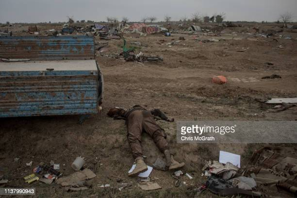 A body reported to be an Islamic State fighter is seen next to a destroyed vehicle in the final ISIL encampment on March 24 2019 in Baghouz Syria The...