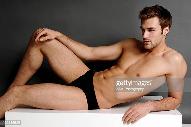 Body shot of an athletic young man in a black bathing trank, lying