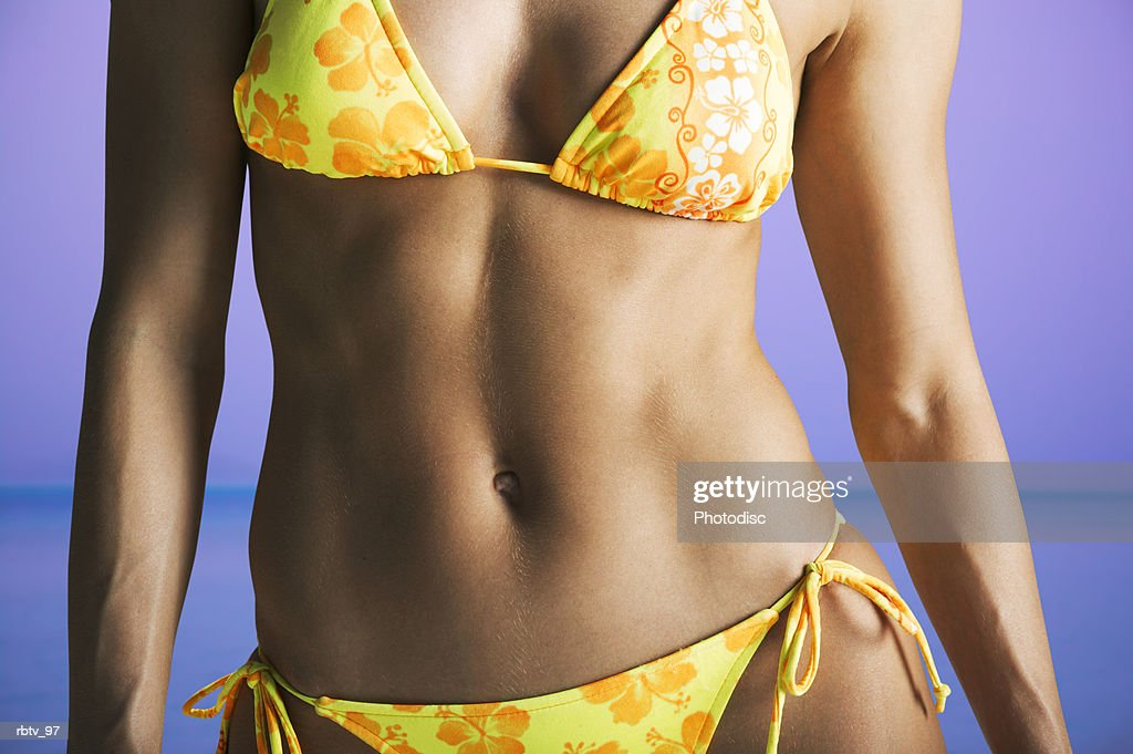 body shot of an in shape a caucasian woman in a yellow bikini at the beach : Foto de stock