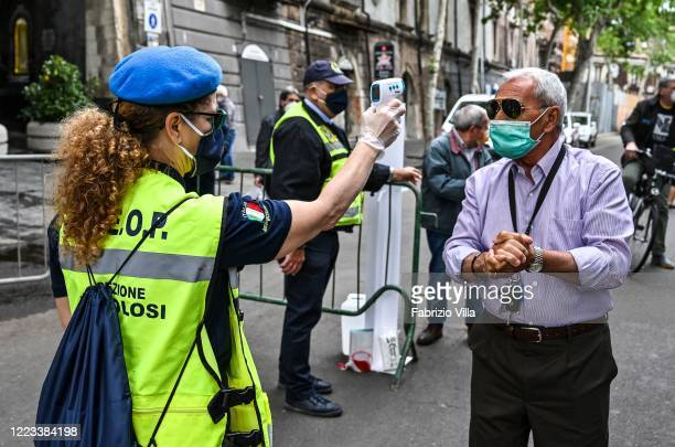 Body temperature control and dispenser with hand gel for customers at the entrance of the historic fish market in Catania called a piscaria with a...