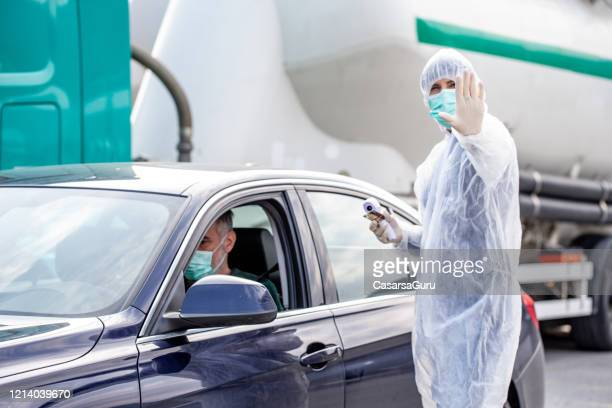 body temperature control before letting anyone entering their country - infrared thermometer stock pictures, royalty-free photos & images