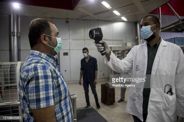 Body temperature of a Turkish man, wearing a face mask as a preventive measure against the coronavirus pandemic, is being measured as Turkish...