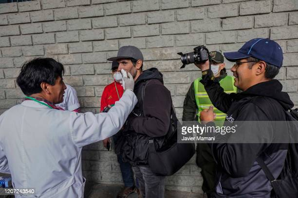 Body temperature of journalists and players is checked by officials of the Health Department health service at the stadium's entrance prior to a...