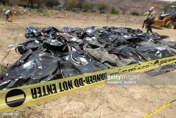 Bodybags containing the remains of people believed to have been slain by jihadists of the Islamic State group lie on the ground at the Speicher camp...