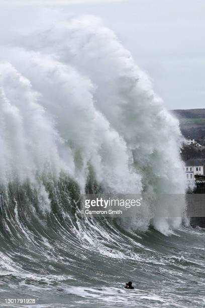 Bodyboarder attempts to take photos in the sea as the waves crash against the Newlyn pier on February 12, 2021 in Newlyn, England. High winds across...