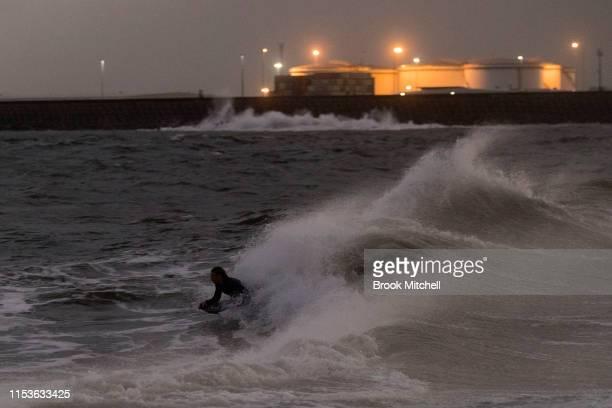 A bodyboarder enjoys rare waves inside Botany Bay after dark on June 04 2019 in Sydney Australia The Bureau of Meteorology issued a severe weather...