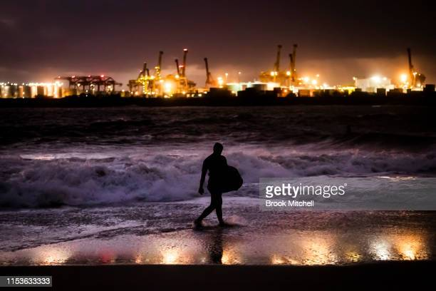 A bodyboarder leaves the water after surfing rare waves inside Botany Bay on June 04 2019 in Sydney Australia The Bureau of Meteorology issued a...