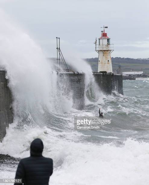 Bodyboarder waves to people watching as he attempts to ride the waves as they crash against the Newlyn pier on February 12, 2021 in Newlyn, England....