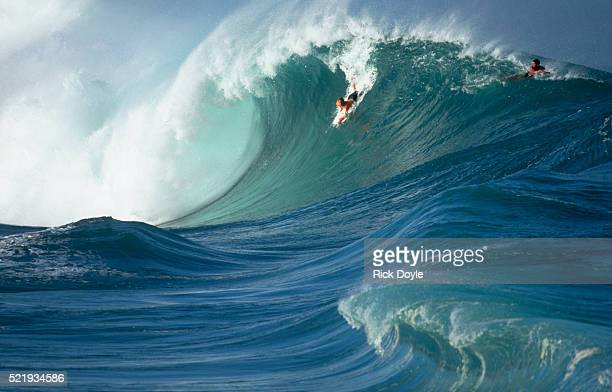 bodyboarders dropping into a wave in waimea bay - waimea bay stock pictures, royalty-free photos & images