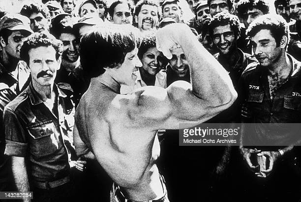Bodybuilder Arnold Schwarzenegger shows off his biceps to IDF soldiers in 1977 in Israel