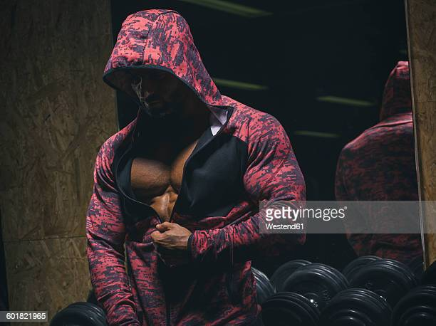 Bodybuilder closing his zipper hoodie in front of a dumbell rack in a gym