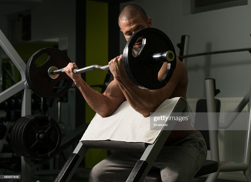 Bodybuilder Exercising Biceps With Barbell : Stock Photo