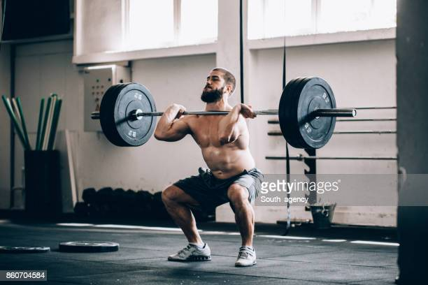 bodybuilder exercising with barbells in the gym - snatch weightlifting stock photos and pictures