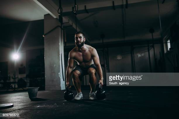 Bodybuilder exercising with kettlebells in the gym