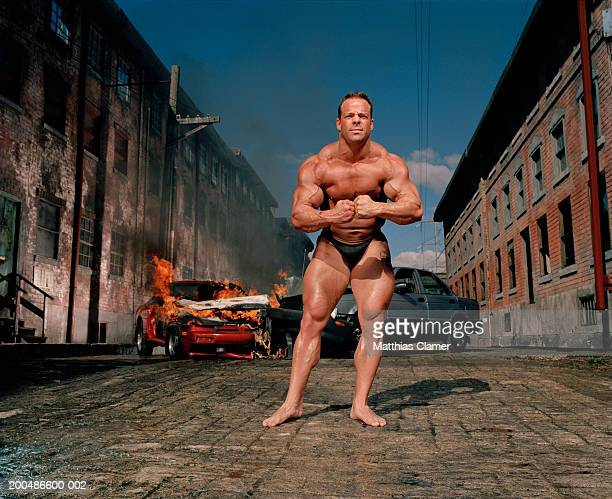 Bodybuilder flexing, car collision in background