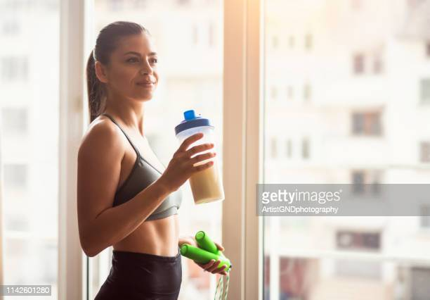 bodybuilder girl relax after exhausting training, young athlete drinking sports drink after workout, beautiful woman resting after exercising training. - protein drink stock pictures, royalty-free photos & images