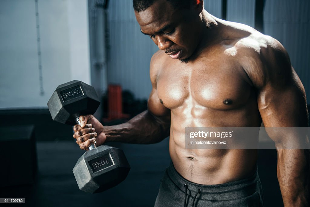 Closeup Of A Muscular Young Man Lifting Dumbbells Weights