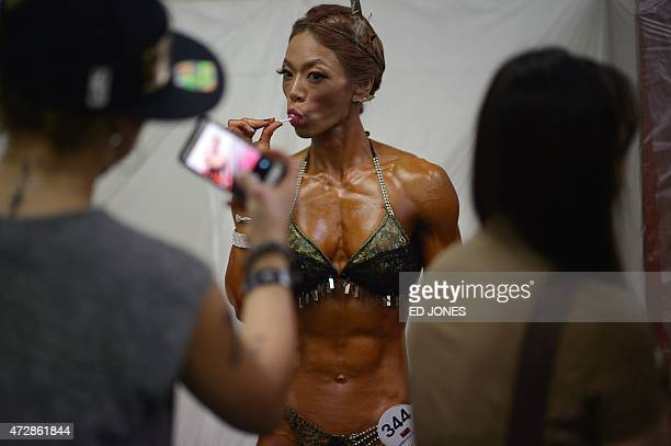 A bodybuilder of the 'Miss Athletic Korea Pro' category poses for photos prior to competing at the 2015 Muscle Pump NABBA WFF Korea Championships in...