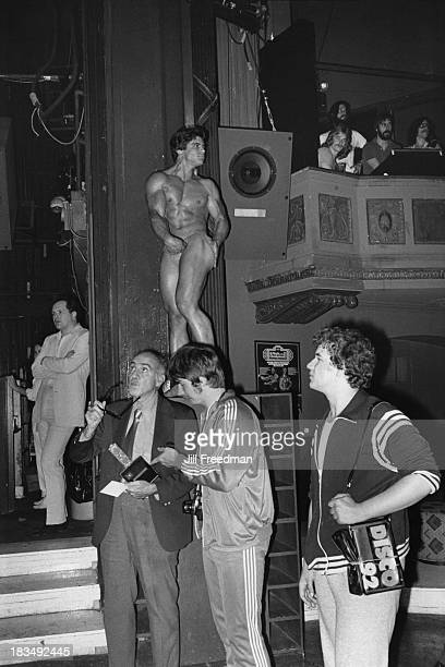 A bodybuilder poses on a raised platform in a nightclub in Midtown Manhattan New York City 1979