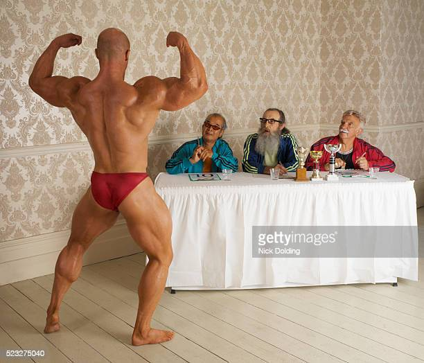 bodybuilder posing for panel of senior judges - bodybuilding stock-fotos und bilder
