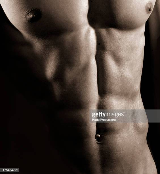 bodybuilder posing on black background. - sexy male torso stock pictures, royalty-free photos & images
